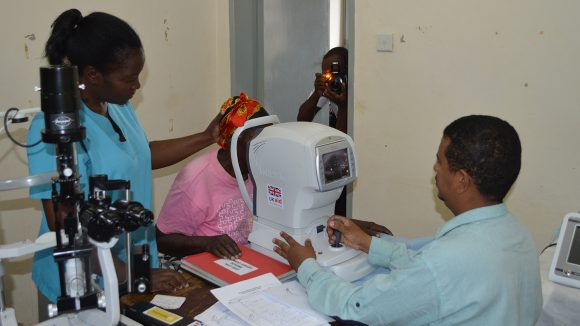 Inuto helps to examine someone's eyes.