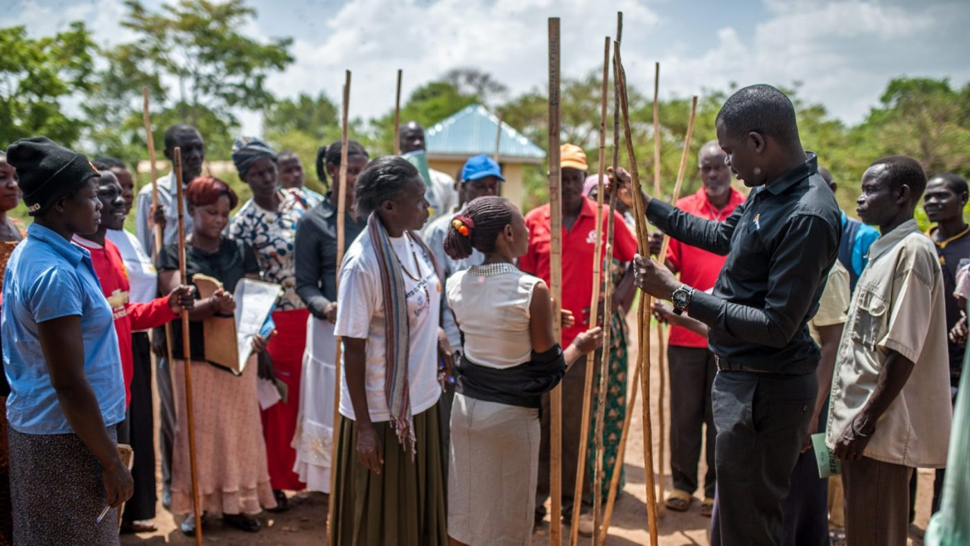 Many people standing holding wooden sticks.