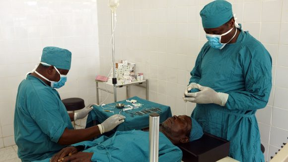 Two surgeons dressed in scrubs prepare to carry out a cataract operation on a patient.