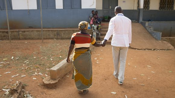 A cataract patient is led into hospital by a doctor in Mozambique.