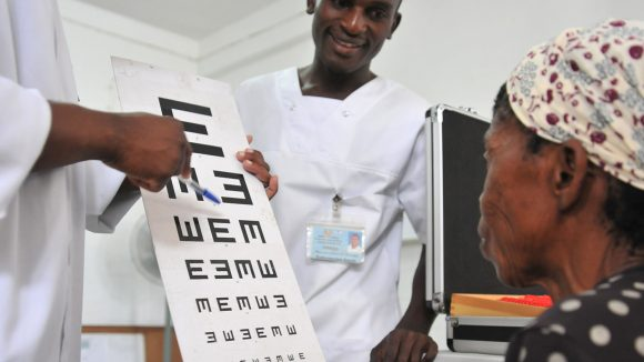 A woman reads from a chart during a sight test in Mozambique.