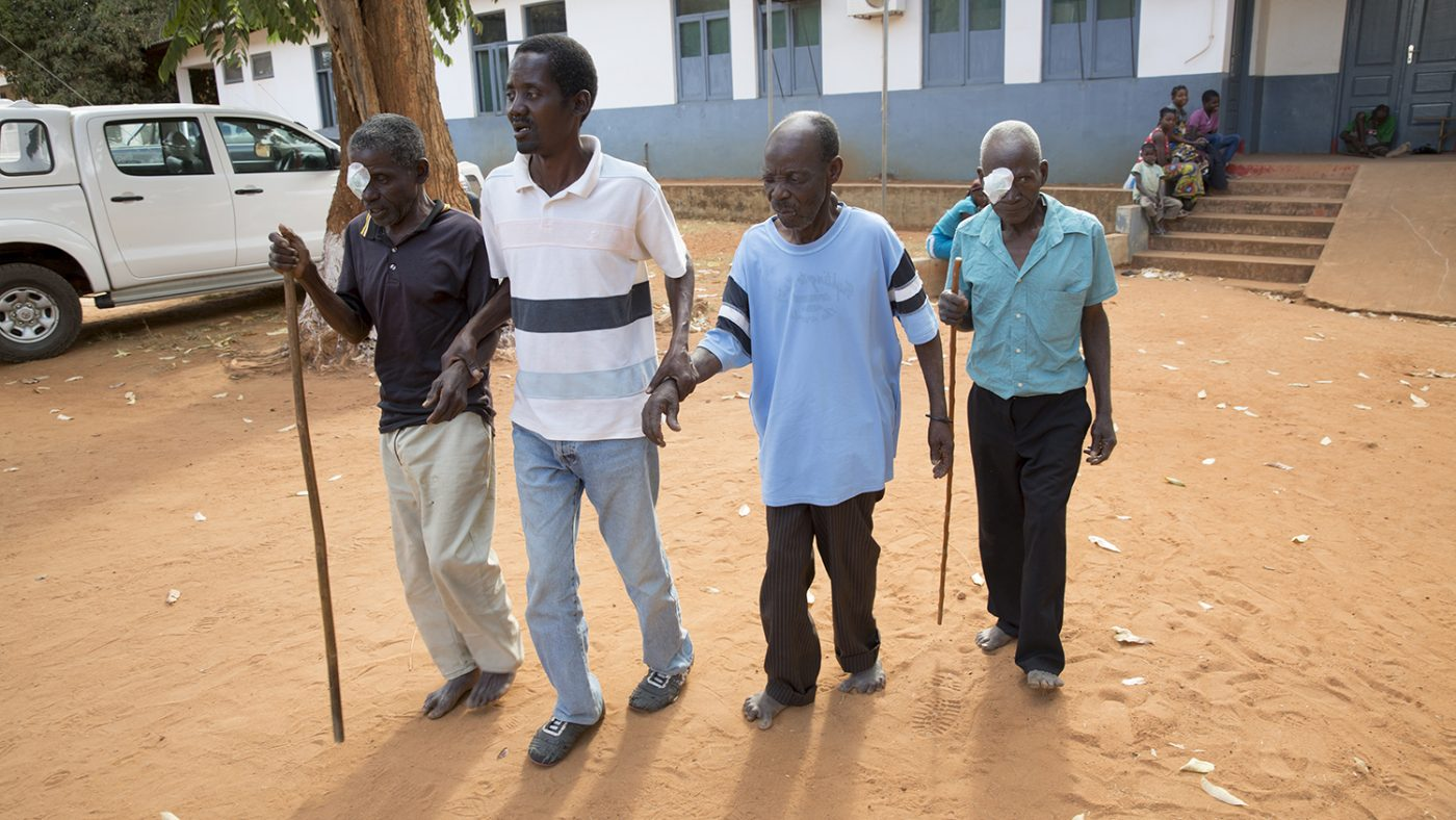 Four men link arms as they leave hospital following cataract surgery in Mozambique.