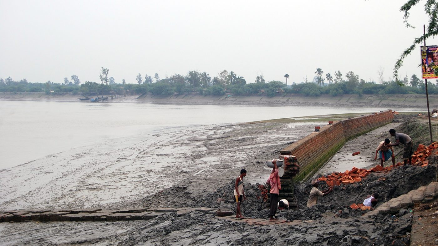 Two men stand on the shoreline in the Sundarbans.