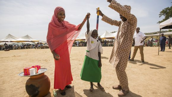 Seven-year-old Dorcas celebrates with the villagers after receiving her treatment for NTDs.