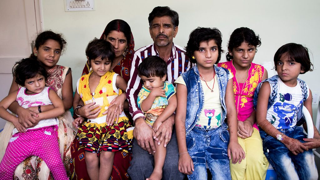 All nine members of the Yadav family sit for a photo.