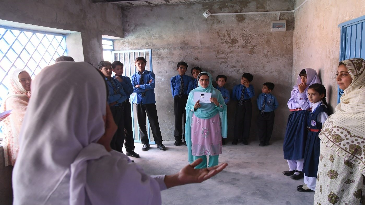 A school teacher doing initial screening for checking eye sight of students.