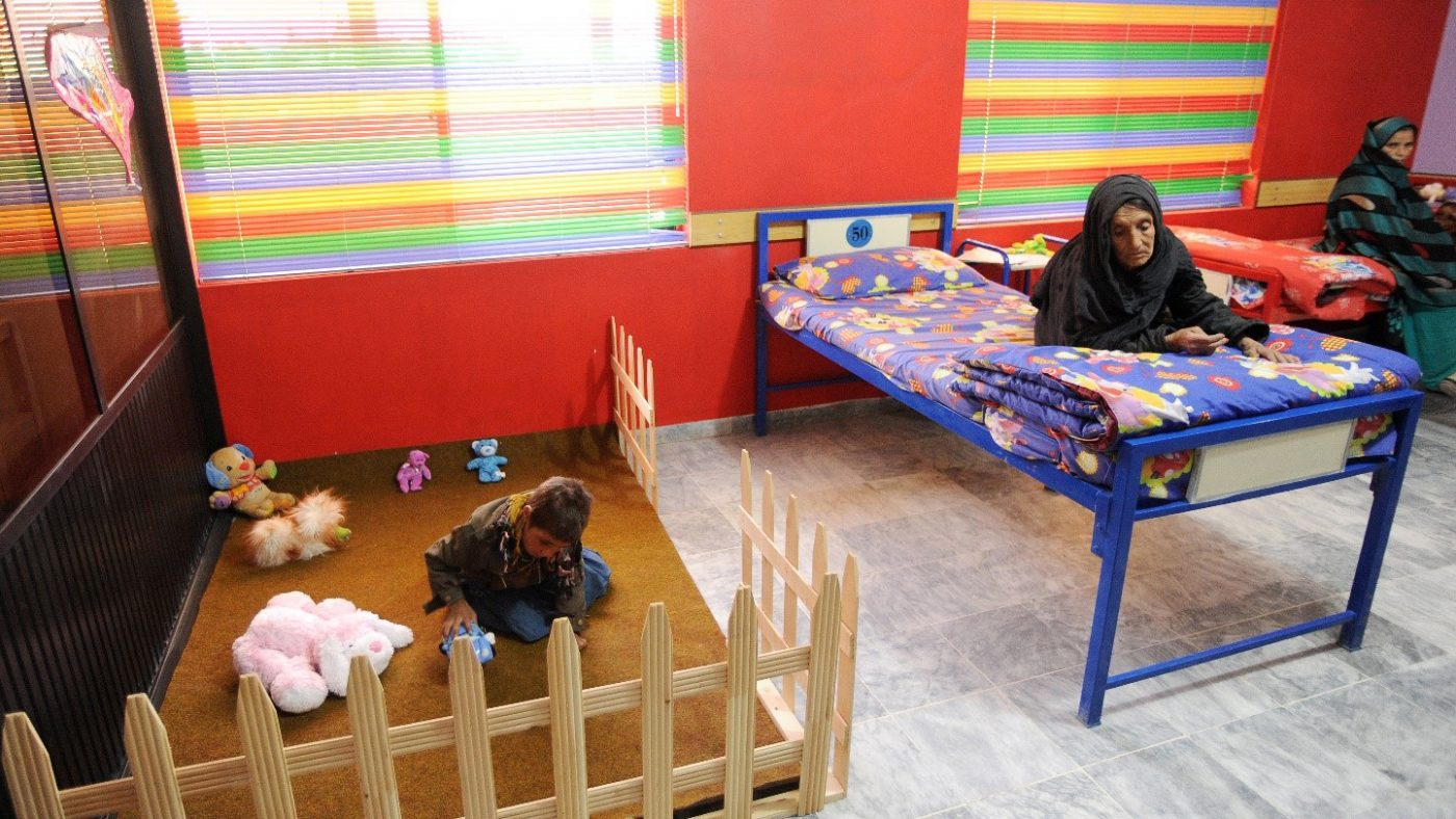 Two women sit on beds while a child plays in a childrens play area.