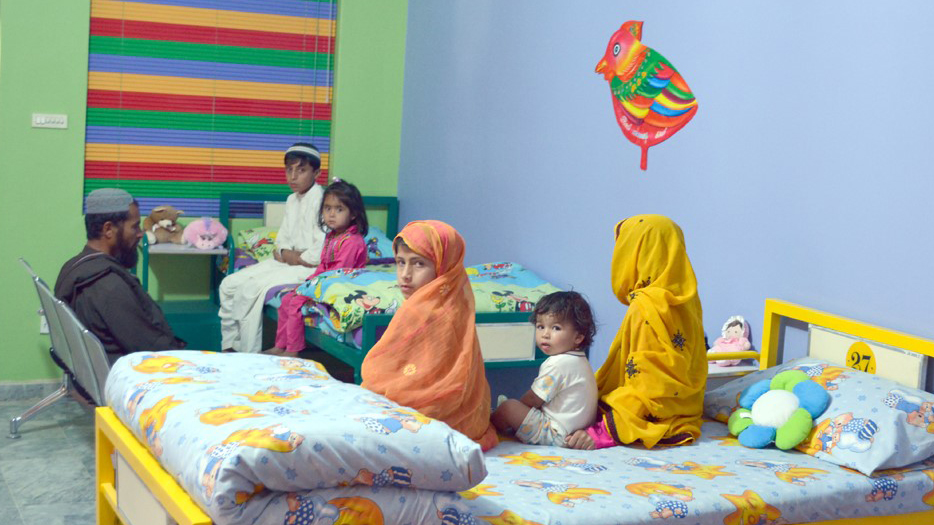 A family sits on a bed in a hospital ward.
