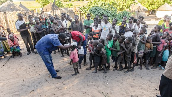 Dr Ndalela is shown screening a queue of young children for trachoma, in Zambia.
