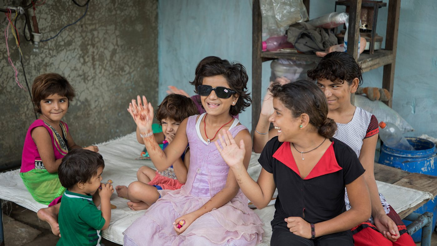 Muskan sits on a bed at home, surrounded by her siblings, all smiling and waving at the camera. She is wearing sunglasses that will protect her new lenses from the sun.