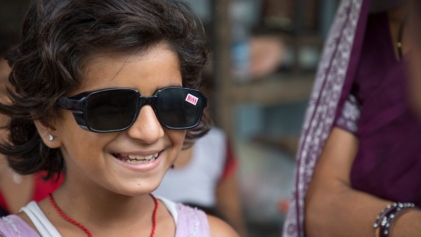 Muskan back at home, smiling with her sunglasses on.