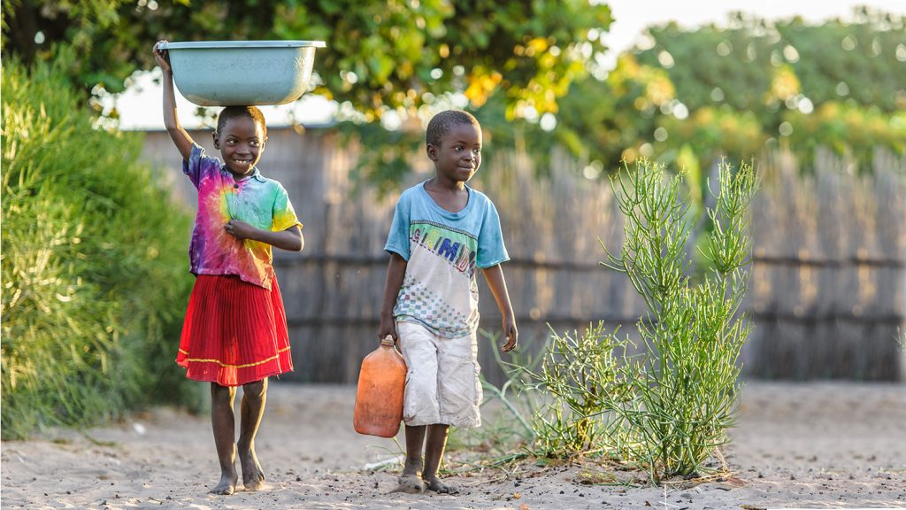 Namukolo and her brother carry water buckets through their village.