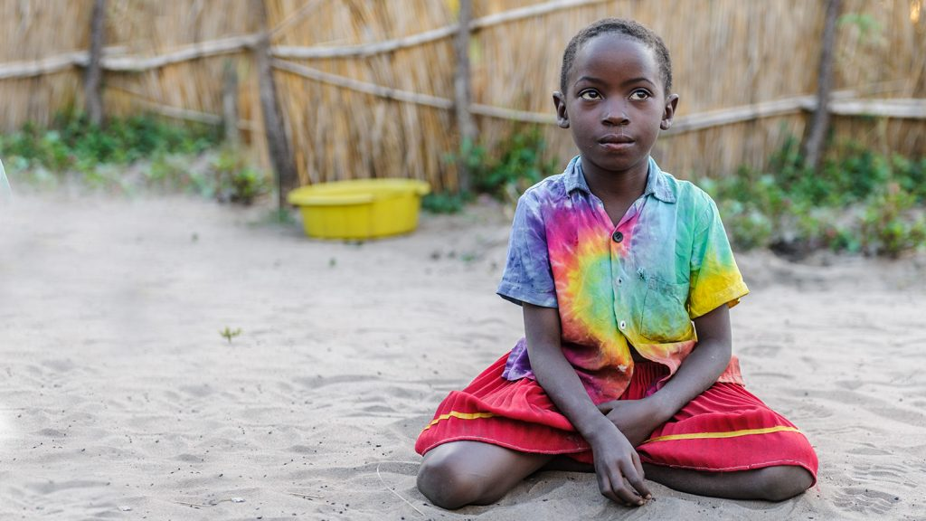 Namukolo sits on a sandy floor in her village.