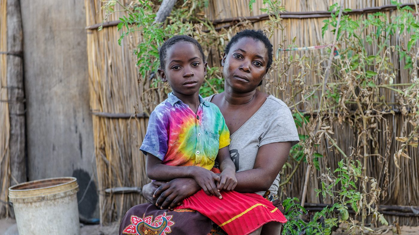 Namukolo sits on her mother's lap.