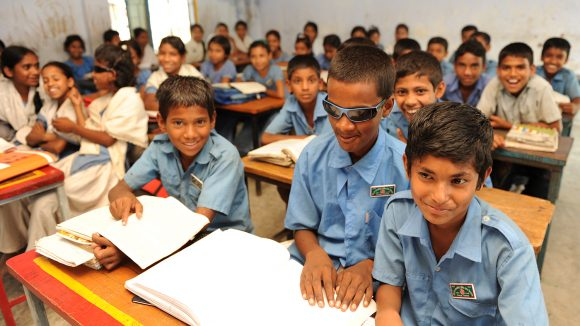A blind schoolboy smiles alongside his classmates in Bangladesh.
