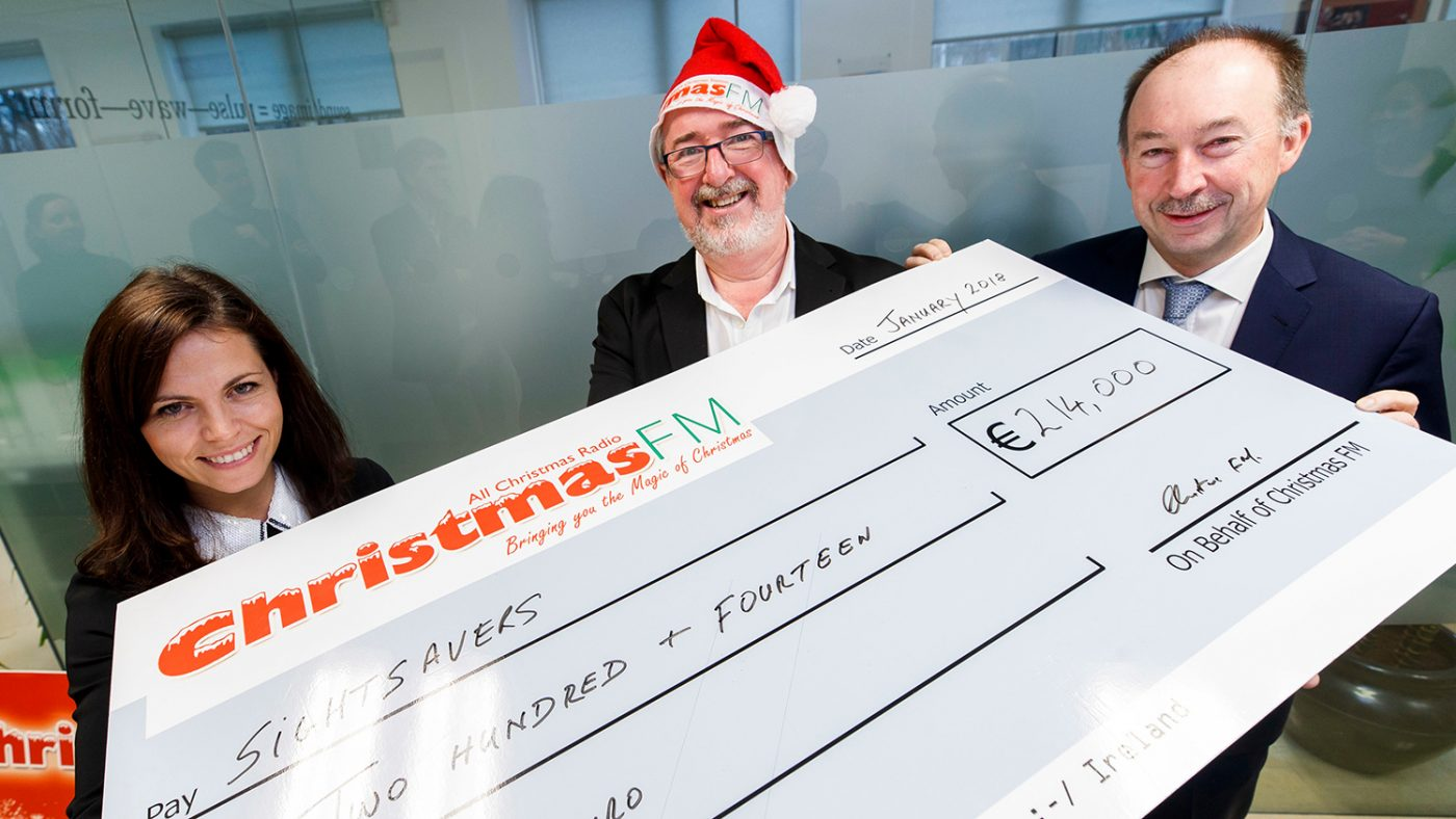 Staff from Sightsavers and Christmas FM hold a giant cheque made out for €214,000.