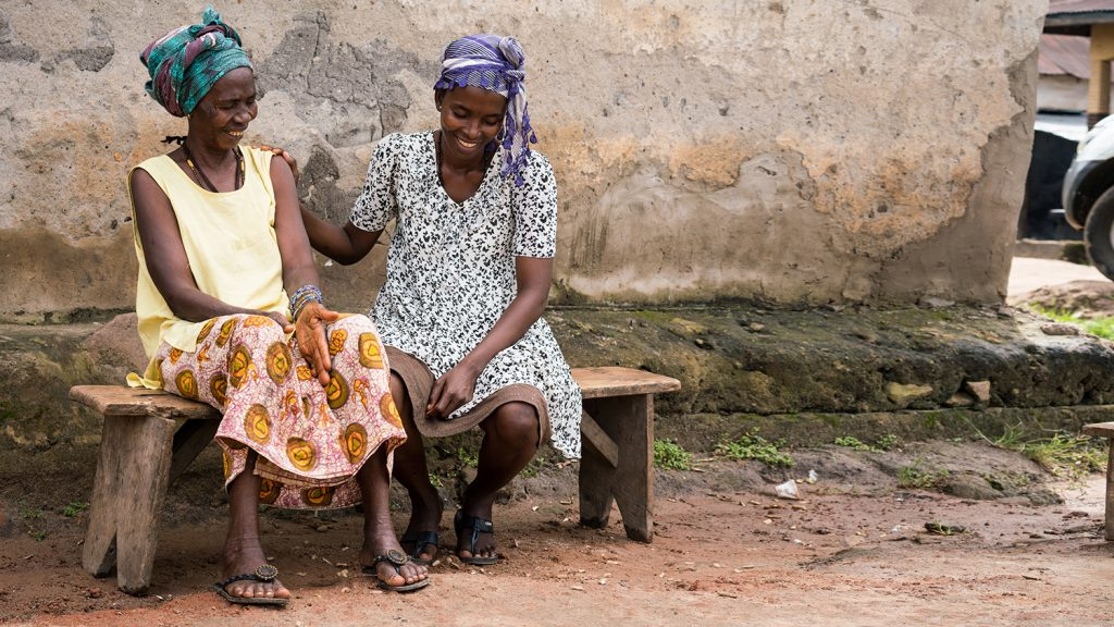 Haja and her mother Kadiatu laugh with each other.