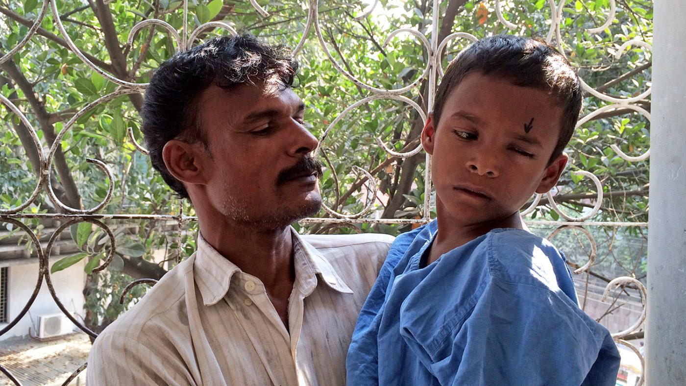 Majidul waits with his father in the hospital ahead of his cataract operation.