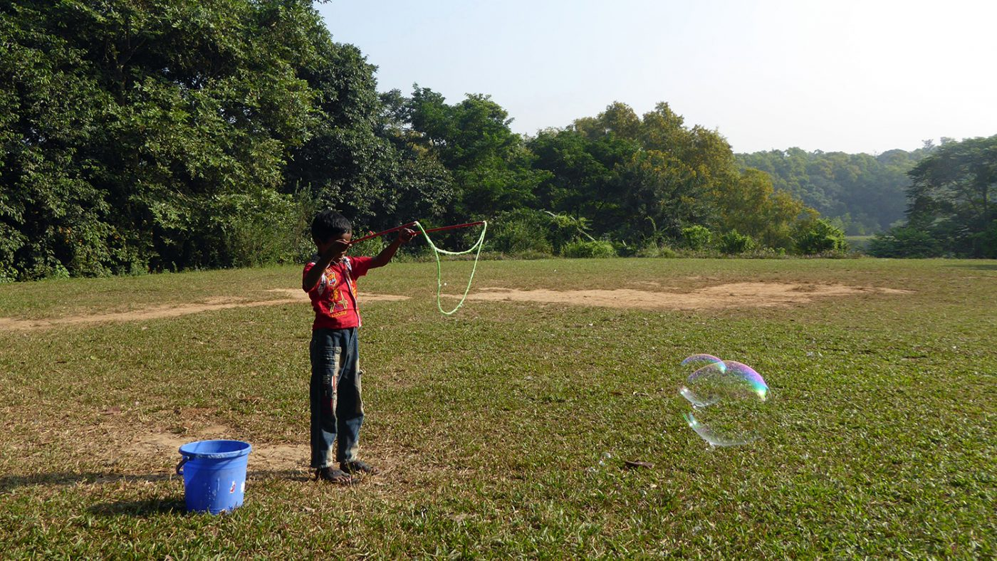 Majidul plays with bubbles in a grassy field.