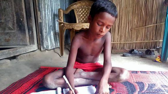 Majidul sits at home writing in his notebook.