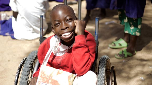 A young boy in a wheelchair smiles after having his eyes tested.