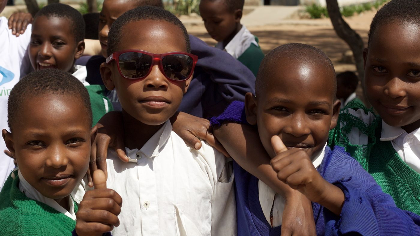 Three boys give a thumbs up after having their eyes tested.