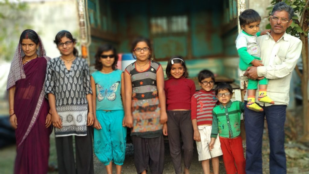 The Yadav family stand in a row for a photo that shows them all in glasses or sunglasses, following their surgeries.