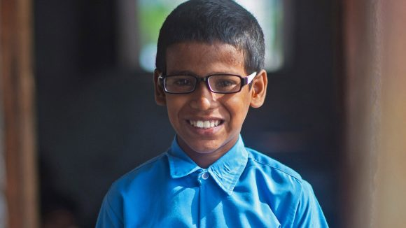 Shahid wearing his new glasses, and a huge grin.