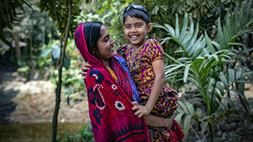 A women in Bangladesh holds her daughter in her arms, both are very happy.