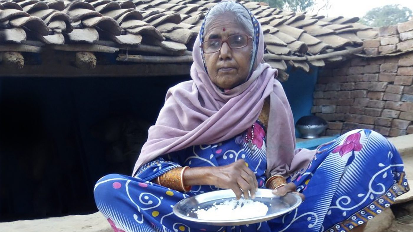 Kusum cleans wheat at her home after her cataract surgery.