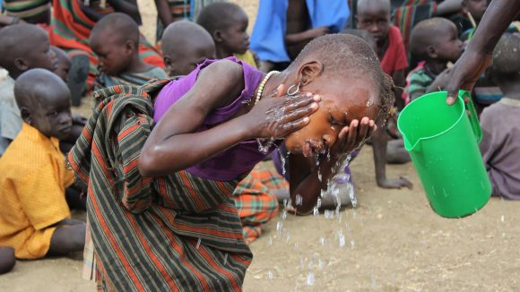 A child washes their face.