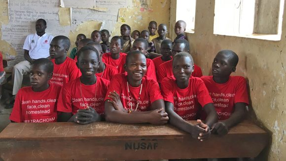 A group of smiling children in a classroom in Uganda.