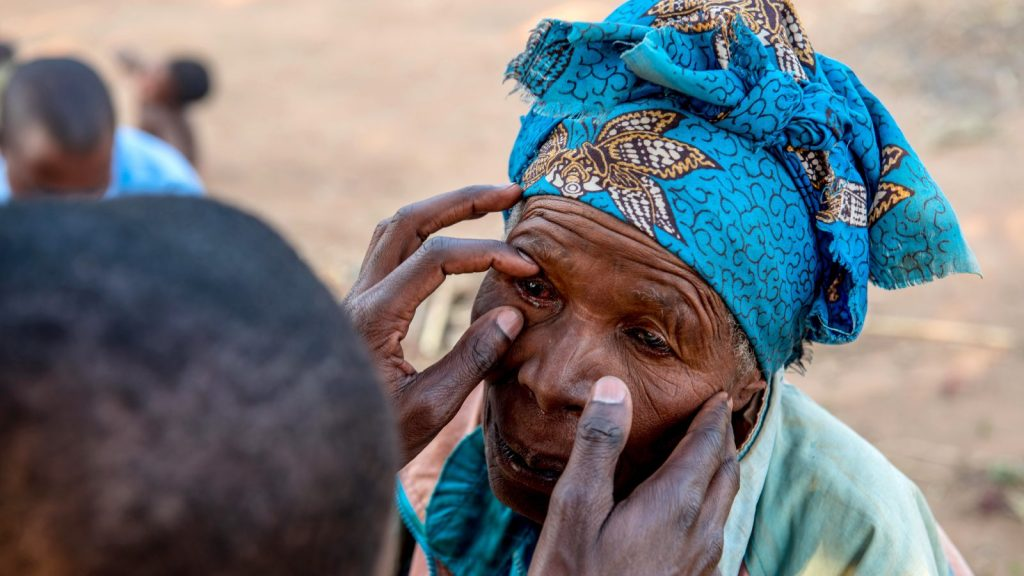 A woman in Malawi has her eyes checked by a health worker.