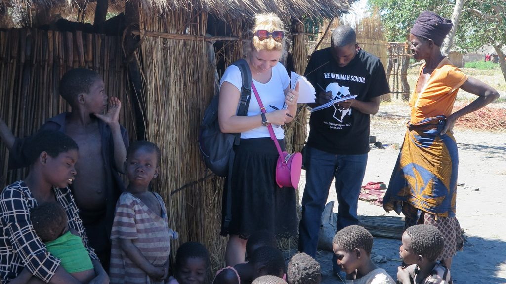Sightsavers' Jo Howard, stands in the shade and talks to the villagers.