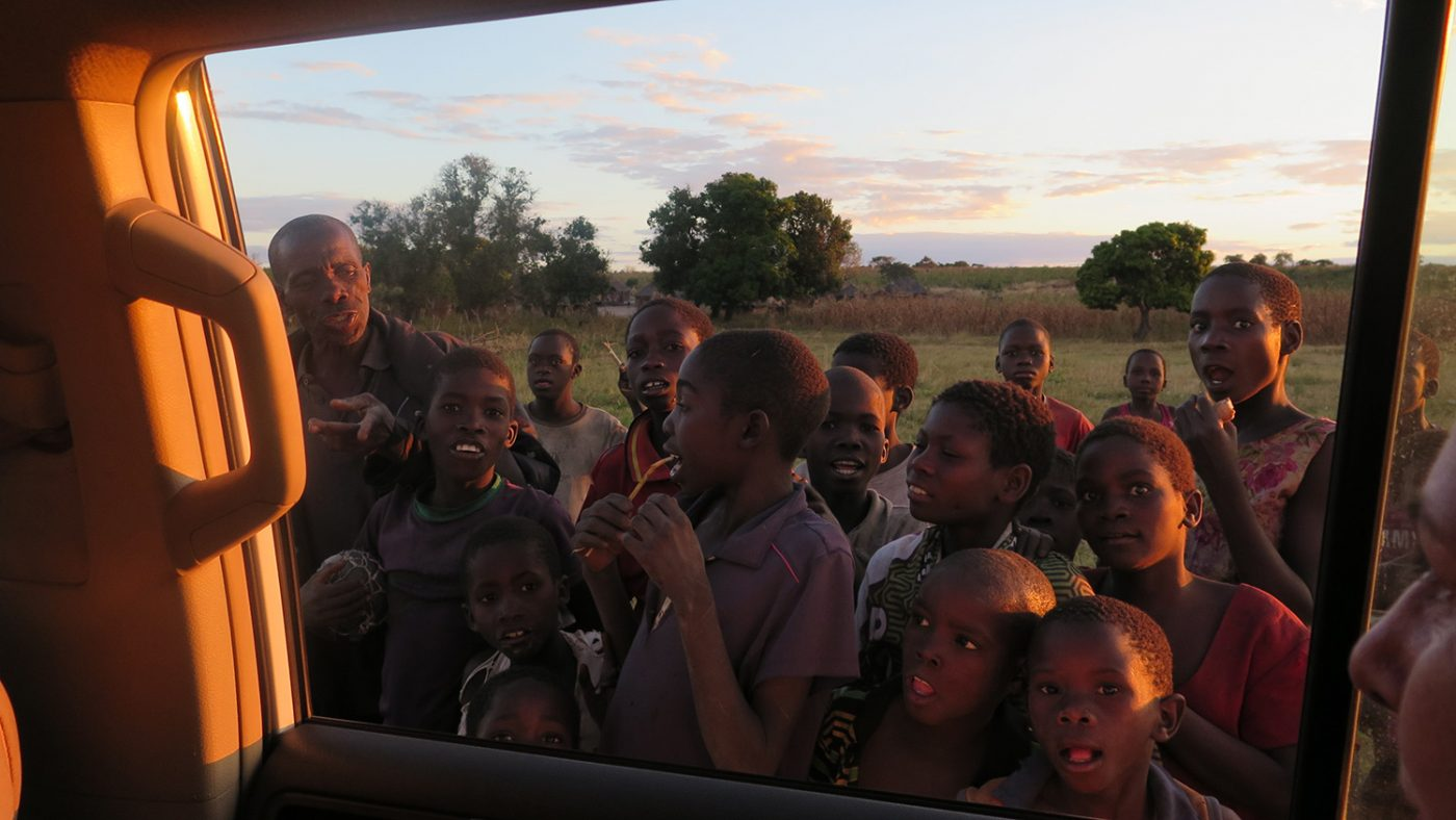 Many children from the village gather by a car window to wave goodbye to the Sightsavers workers.