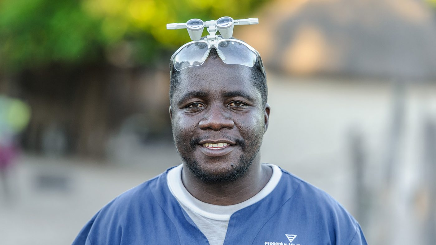 Mr Ndalela stands with his examination glasses on his head, smiling at the camera.