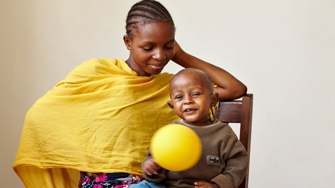 Baraka sits on his mother's lap and waves a yellow balloon.