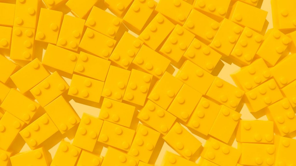 A pile of yellow Braille Bricks, which feature braille characters on the top to help children learn braille.