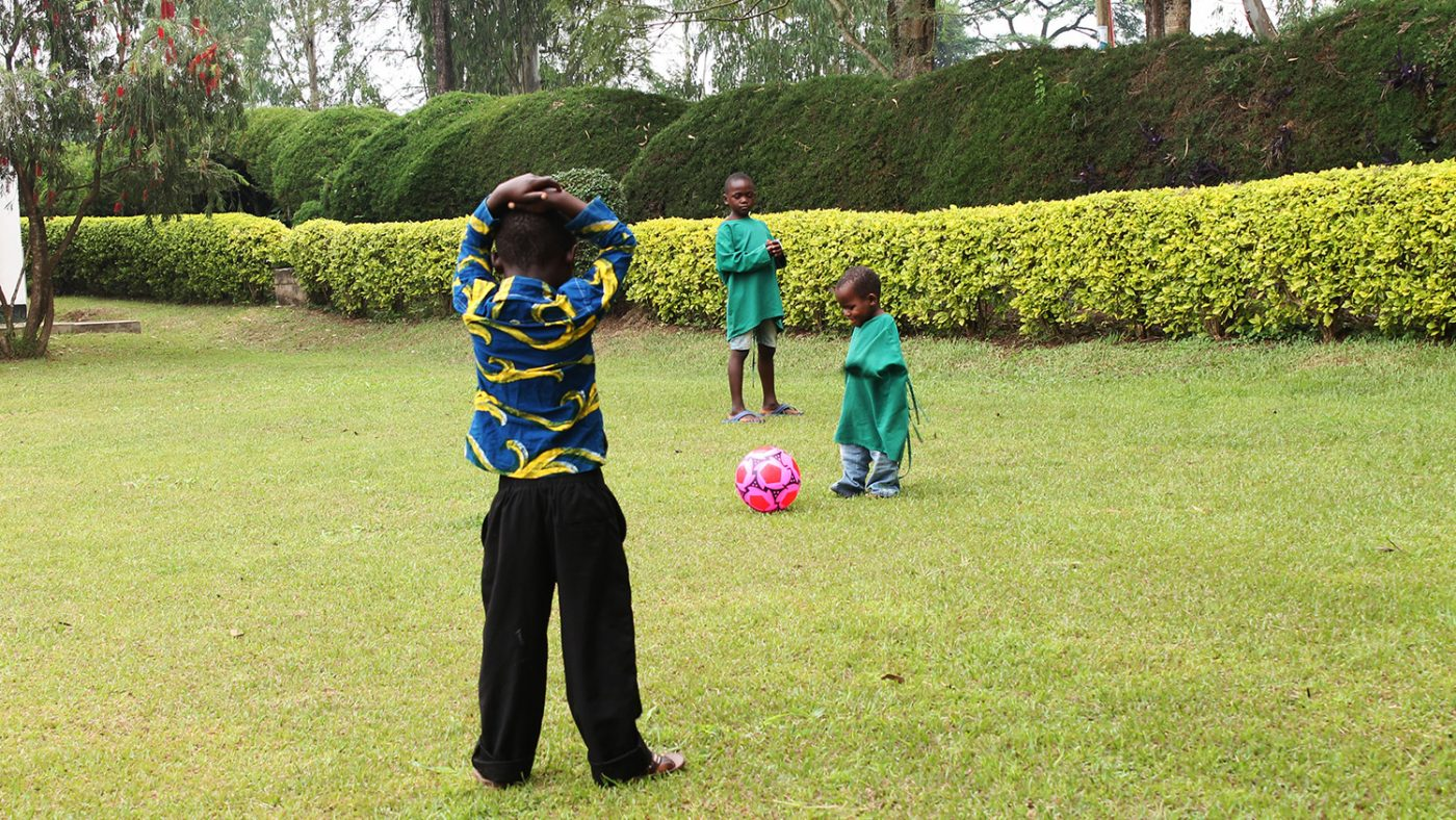 Winesi runs for a pink football in a small game of football on the hospital lawns.