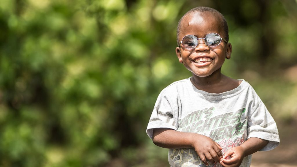 Criscent proudly wearing his new glasses, as he stands in some woods on the way to his village in Uganda.
