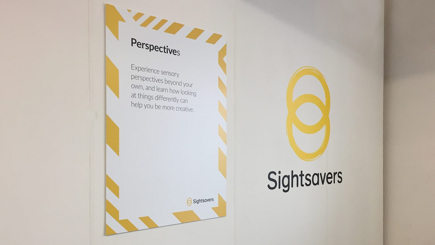 The front of Sightsavers' stand, featuring a logo and a sign with the word 'Perspectives'.