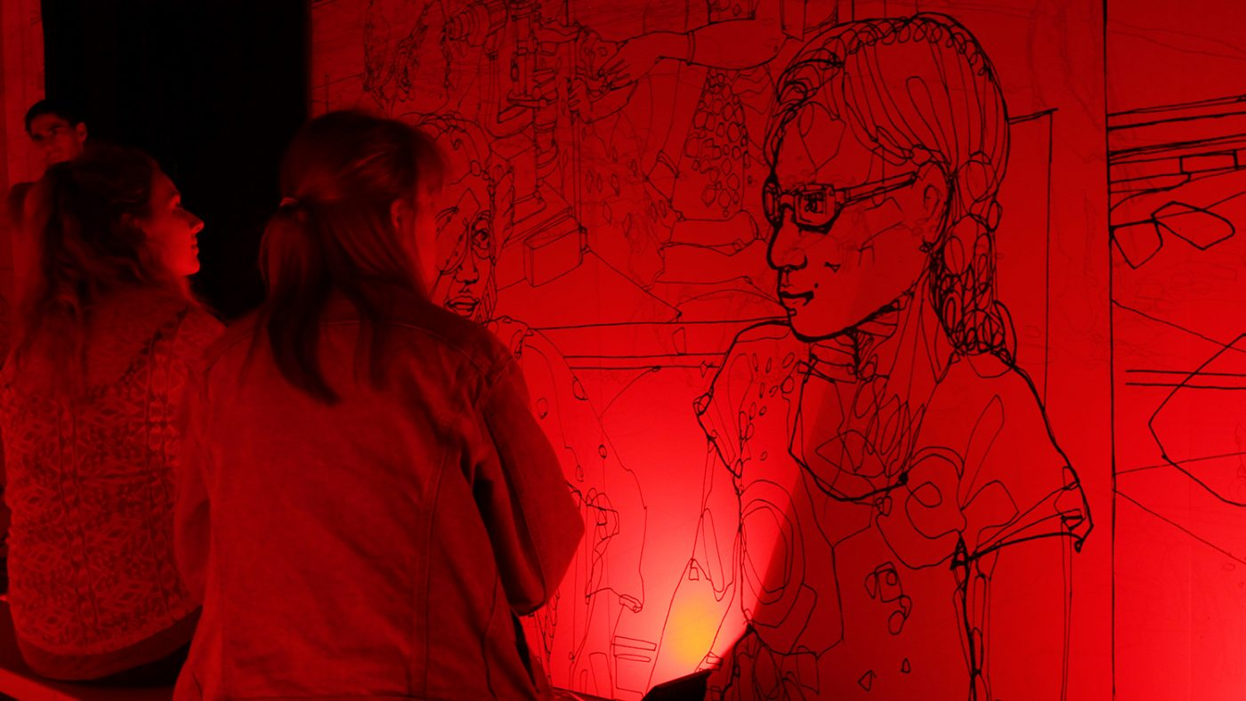 Inside the colour room, which is bathed in red light to reveal an illustration of a girl on the wall.