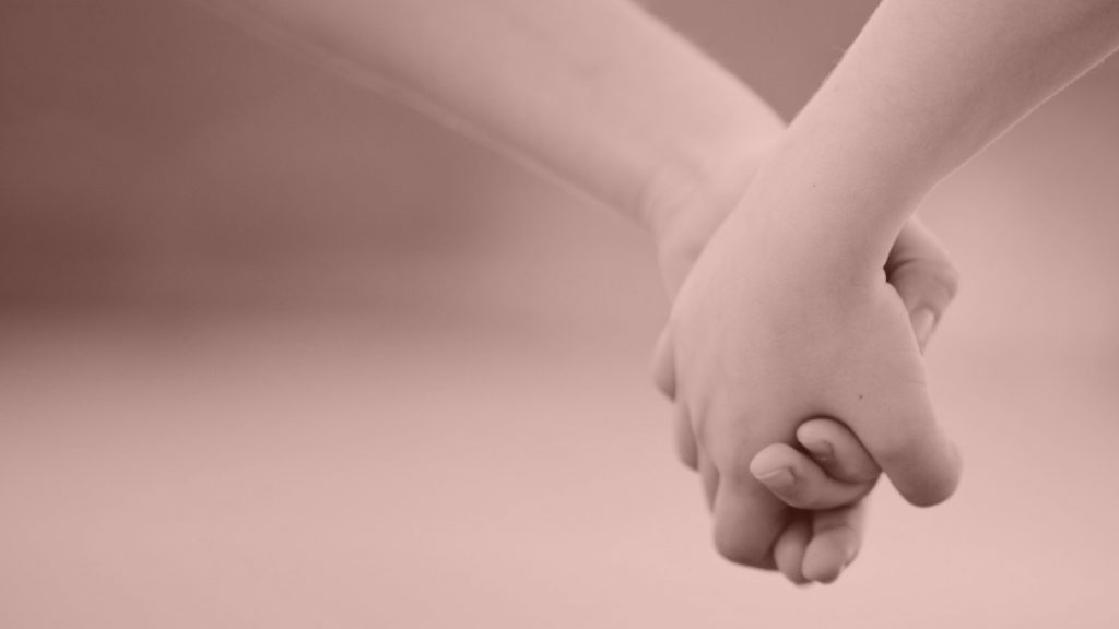 A close-up of two people holding hands.