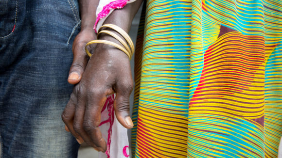 A close up of two women holding hands.