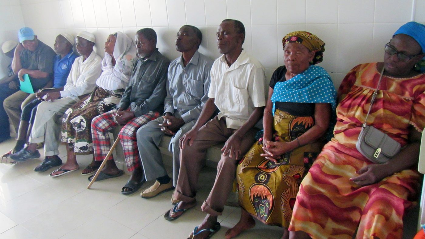 A queue of patients sitting outside the clinic.