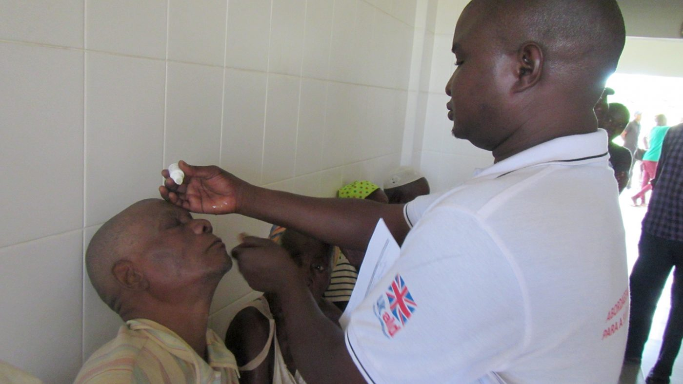 An eye health worker puts eye drops into a patient's eyes.
