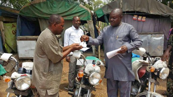 NTD coordinators in Nigeria receive the keys to their new motorbikes from the Director of Public Health.