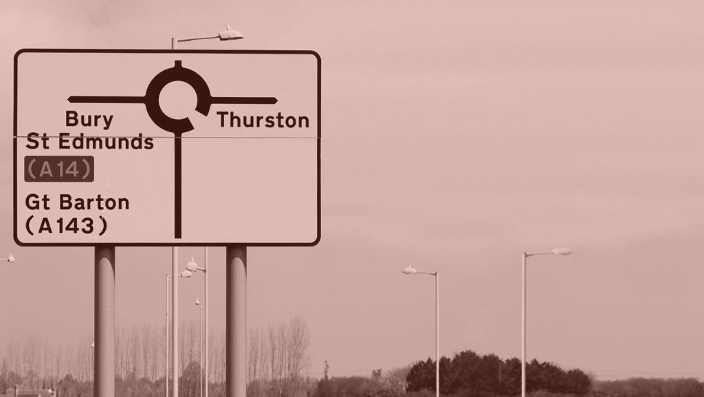 A road sign featuring the Transport font, with the words 'Bury St Edmunds (A14), Gt Barton (A143) and Thurston' plus a roundabout symbol.