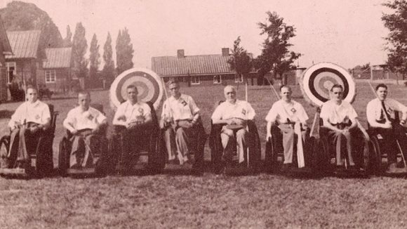 The archery competitors from the Stoke Mandeville Games line up on the field in front of their archery targets.