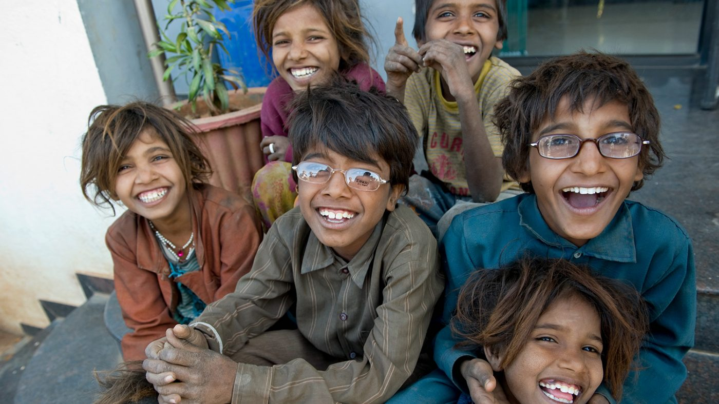 A group of six children sit on the floor, some have glasses and all of them are smiling.
